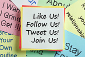 Like Us, Follow Us, Tweet Us and Join Us written on a note paper. Concept of social media marketing and management.