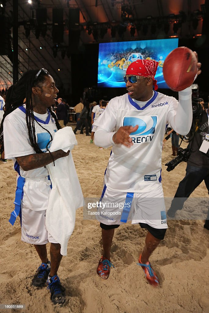 Lil Wayne (L) and Deion Sanders attend DIRECTV'S Seventh Annual Celebrity Beach Bowl at DTV SuperFan Stadium at Mardi Gras World on February 2, 2013 in New Orleans, Louisiana.