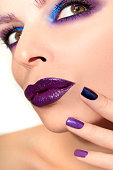 Lilac makeup and manicure on nails woman closeup.