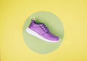 Lilac sneakers on a multi colored pastel surface. Top view, Fashion style.