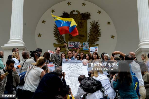 Lilian Tintori wife of jailed Venezuelan opposition leader Leopoldo Lopez displays a poster with the list of names of political prisoners before a...