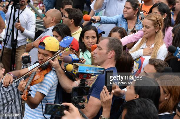 Lilian Tintori wife of Venezuelan political prisoner and opposition leader Leopoldo Lopez listens to an opposition activist playing the violin during...