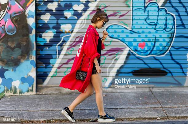 Liliy Zhang wearing a long red light jacket with a peace print from You Planet black leather shorts a black tshirt a black Chanel bag and black...