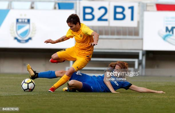 Lilla Turanyi of MTK Hungaria FC slide tackles Gulnara Gabelia of WFC BIIKKazygurt during the UEFA Women's Champions League Qualifying match between...