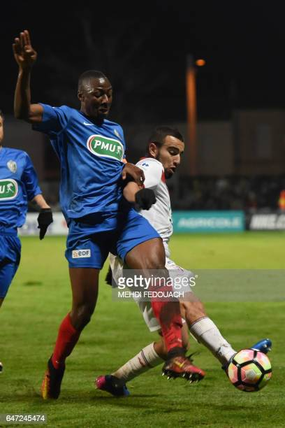 Lille' s French Algerian midfielder Naim Sliti vies with Bergerac's French defender Mamadou Kamissoko and French midfielder Victor Fuchs during the...