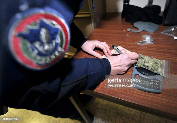 A Lille's French customs officer weighs sealed marihuana he seized on February 3 2011 at the Rekkem FrancoBelgian border checkpoint in...