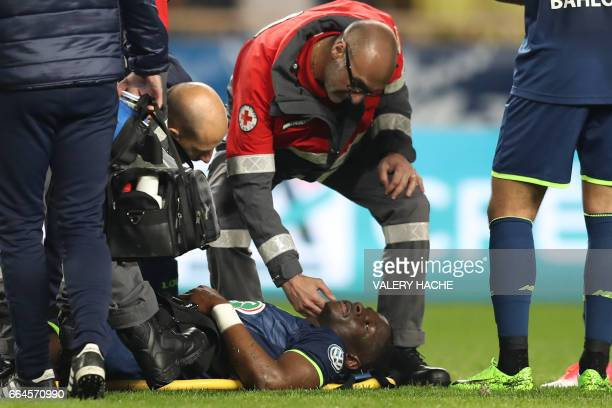 Lille's French defender Adama Soumaoro is treated by medical staff after an injury during the French Cup quarter final football match between Monaco...