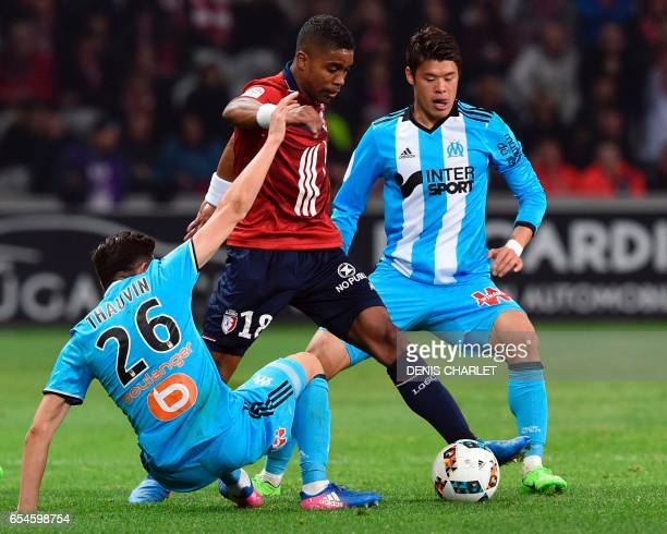 Lille's French defender Franck Beria vies with Olympique de Marseille's French midfielder Florian Thauvin and Olympique de Marseille's Japanese...