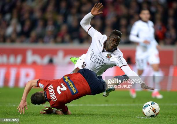 Lille's French defender Sebastien Corchia falls with Nice's Italian forward Mario Balotelli during the French L1 football match between Lille and...