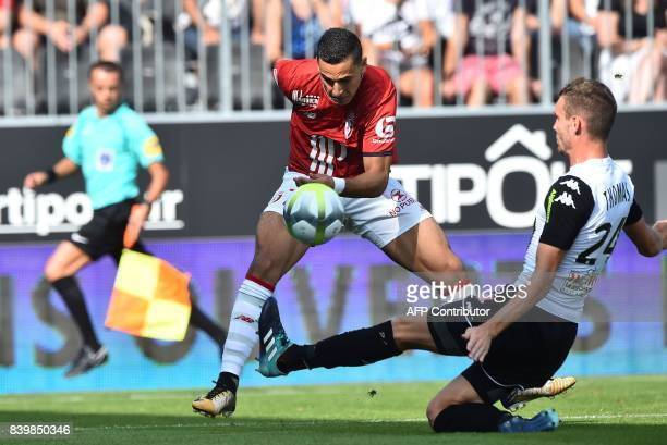Lille's French forward Anwar El Ghazi fights for the ball with Angers' French defender Romain Thomas during the French L1 football match between...