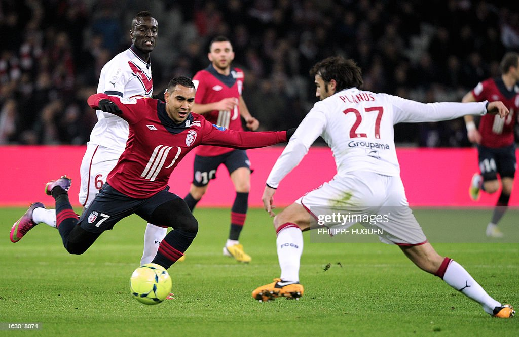 Lille's French forward Dimitri Payet (L) vies for the ball with Bordeaux's French defender Marc Planus (R) during the French L1 football match Lille vs Bordeaux on March 3, 2013 at the Grand Stadium in Villeneuve d'Ascq.
