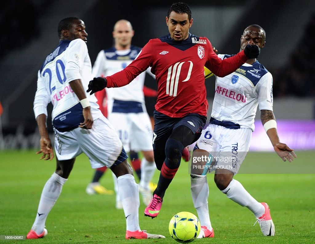 Lille's French forward Dimitri Payet (C) vies with Troyes' French defender Eloge Enza-Yamissi (R) and French-Congolese midfielder Granddi Ngoyi during a French L1 football match between Lille and Troyes on February 2, 2013 at the Grand Stade in Villeneuve d'Ascq.