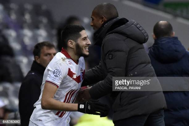 Lille's French forward Yassine Benzia celebrates with his head coach Franck Passi after scoring a goal during the French L1 football match between...