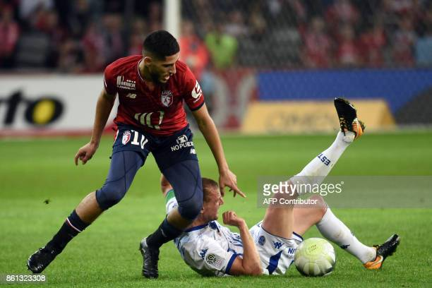 Lille's French forward Yassine Benzia vies with Troyes' French midfielder Stephane Darbion during the French L1 football match between Lille and...