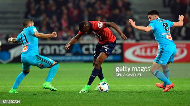 Lille's French midfielder Ibrahim Amadou vies with Morgan Samson and Olympique de Marseille's French forward Dimitri Payet during the French L1...