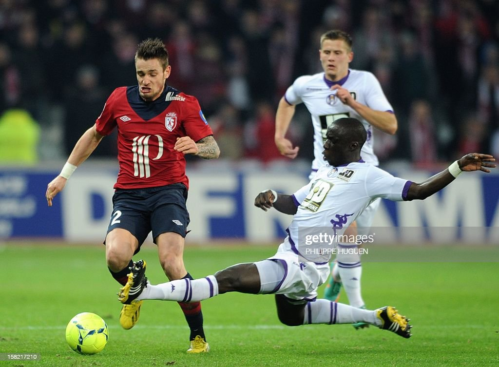 Lille's French midfielder Mathieu Debuchy (L) vies with Toulouse's French defender Cheikh M'bengue during the French L1 football match Lille vs Toulouse on December 11, 2012 at the Grand Stade Stadium in Villeneuve d'Ascq.