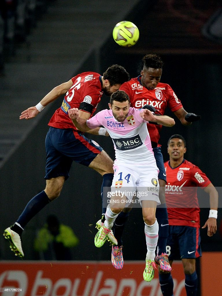 Lille's Montenegran defender Marko Basa (L) and Lille's French midfielder Soualiho Meite vie for the ball with Evian's French midfielder Cedric Barbosa (C) during the French L1 football match between Lille (LOSC) and Evian (ETGFC) on January 7, 2015 at the Pierre-Mauroy stadium in Villeneuve-d'Ascq, northern France. AFP PHOTO / DENIS CHARLET