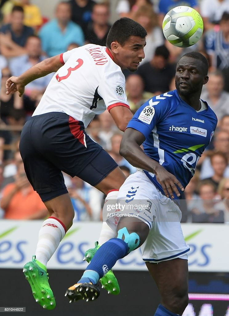 Lille's Paraguay defender Junior Alonso (L) fights for the ball with Strasbourg's Senegalese defender Kader Mangane during the French L1 football match between Strasbourg (RCSA) and Lille (LOSC) at The Meinau Stadium in Strasbourg, eastern France on August 13, 2017. /