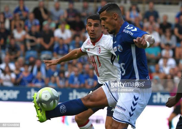 Lille's Paraguay defender Junior Alonso fights for the ball with Strasbourg's Algerian forward Idriss Saadi during the French L1 football match...