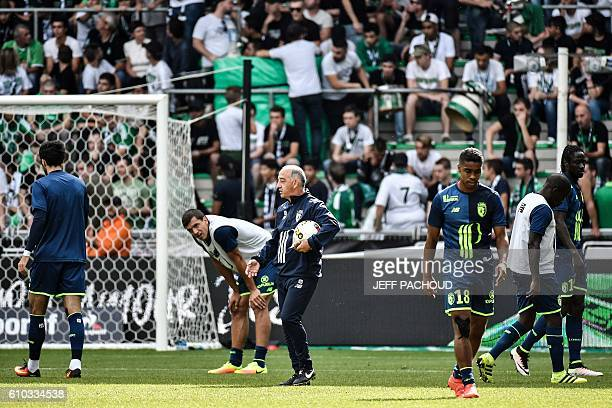Lille's players warm up with assistant coach JeanMarie De Zerbi ahead of the L1 football match between AS SaintEtienne and Lille at the Geoffroy...