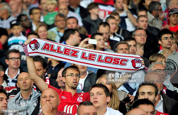 A Lille's supporter holds his team banner during the end of the UEFA Champions League preliminary round football match Lille vs Copenhagen on August...