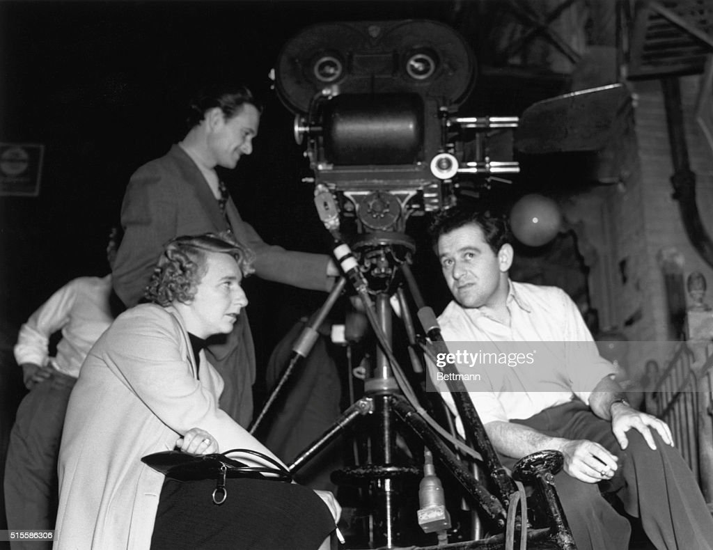 Lillian Hellman, famous playwright and scenarist, discusses script changes with director William Wyler on the set of Samuel Goldwyn's production of 'Dead End.' In the background is Gregg Toland, the cinematographer.