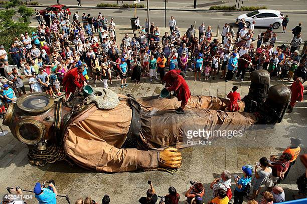 Lilliputions throw buckets of water onto the diver Giant as he sleeps near the Perth train station on Wellington Street during the Perth...