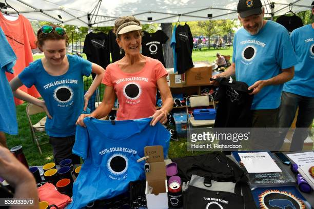 Lilly O'Leary left Linda Hofer second from left and Ronald O'Leary right can barely keep up with demand for their eclipse related tshirts coasters...
