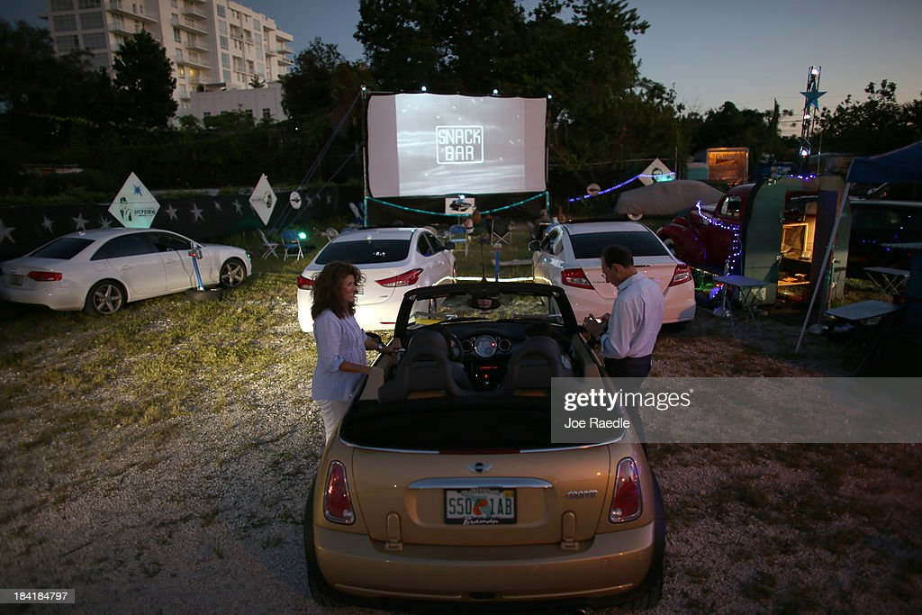 Lily Azel (L) and Jose Azel wait for the start of 'Back to the Future' at The Blue Starlite Mini Urban Drive-In on October 11, 2013 in Miami, Florida. Many traditional drive-in theaters around the United States have closed but the owner of The Blue Starlite held a grand opening for his small outdoor facility, which can accommodate 20 to 24 cars and has seats near the front of the viewing area, with hopes it will become popular in the urban core of Miami.
