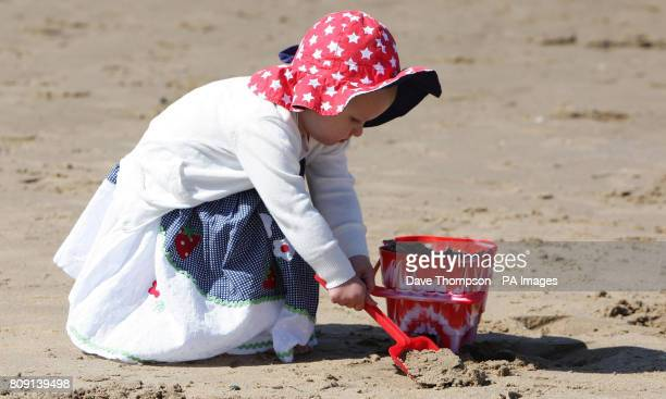 Lily Brown 19 months from Manchester builds a sandcastle on Blackpool beach as the warm weather continues over Easter