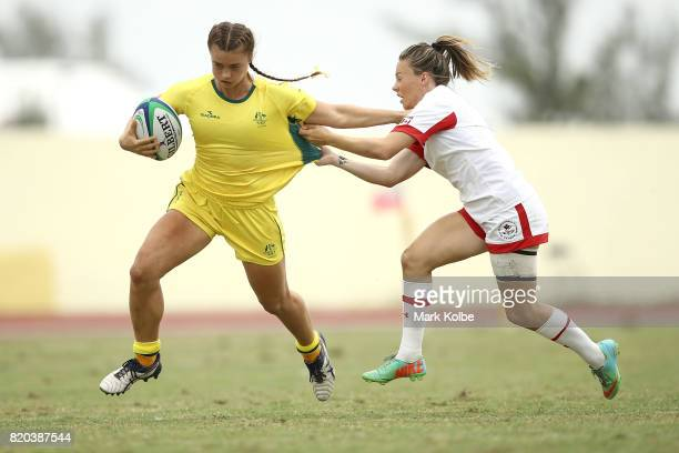 Lily Dick of Australia is tackled by Denise Roy of Canada during the girl's rugby 7's gold medal final match between Austra and Canada on day 4 of...