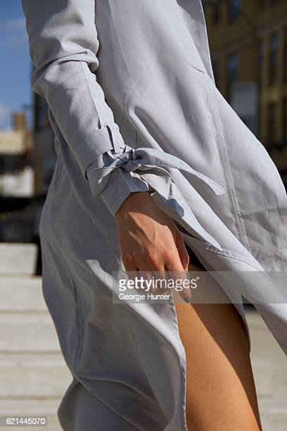Lily Montasser wearing grey silk long tunic top with slit by Vince and Miss Pap grey cotton trench coat with waist tie and wrist ties on November 6...