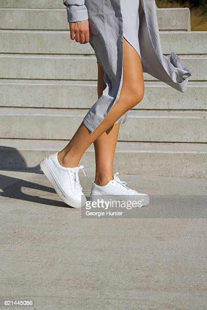 Lily Montasser wearing white DKNY leather sneakers grey silk long tunic top with slit by Vince and Miss Pap grey cotton trench coat with waist tie on...