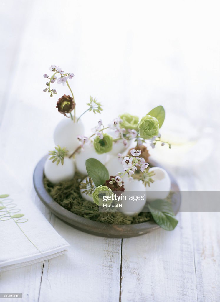 Lily of the valley and lisianthus in eggs on moss : Stock Photo