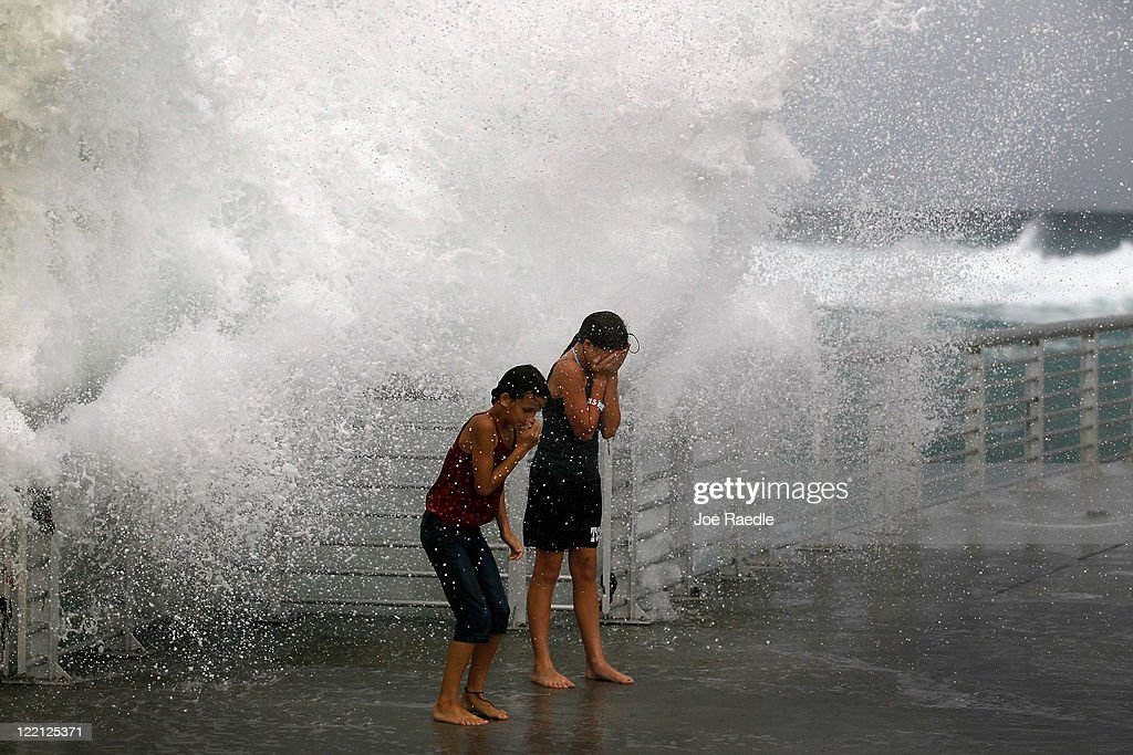 Lilyana Fowler (L) and Isabella Lugli brace themselves as a wave bursts onto a pier at the Boynton Beach inlet on August 25, 2011 in Boynton Beach, Florida. Hurricane Irene is moving over the Bahamas and could still be a major storm as it approaches the North Carolina coast the morning of August 27.