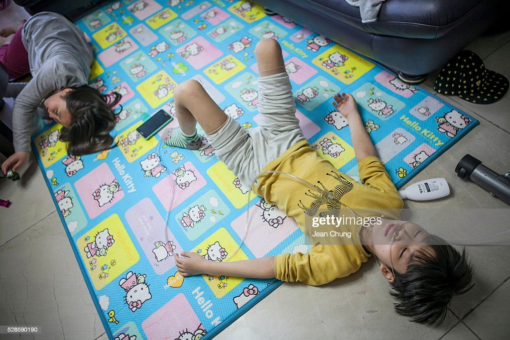 Lim Seong-joon, (R) 13, who is suffering from chronic lung disease, lies down on a matt next to his sister at their home on May 6, 2016 in Yongin, South Korea. His mother bought a humidifier sterilizer called 'Oxy Humidifier on Duty' back in 2003, and used the product with a humidifier for more than a year, subsequently damaging the lungs of Seong-joon. Seong-joon has gone through operations and now is living off of an oxygen tank 24 hours a day. His mother, Kwon Mi-ae, said that she thought of killing herself many times, but decided to live for him. Beginning in 2001, Reckitt Benckiser Korea (known as Oxy prior to 2014) used Polyhexamethylene guanidine (PHMG) in a humidifier sterilizer product called Oxy Ssak Ssak; the ingredient was dropped in 2011 when the Korea Centers for Disease Control and Prevention (KCDC) published a report showing a link between the compound and lung damage and deaths. Several companies in South Korea made humidifier sterliizers with poisonous ingredients between 2001 and 2011. According to a BBC report in May 2016, about 500 people, many of them women and children, are reported to have died or been injured after inhaling these ingredients. One of the victims's fathers is visiting U.K. right now, and a few other victims's families are planning to visit the U.K. at the end of May. The U.K.-based firm Reckitt Benckiser has admitted and apologized for selling a humidifier disinfectant that killed more than 100 people in South Korea on May 2, 2016.