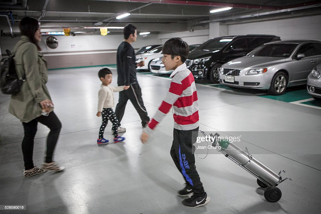 Lim Seong-joon, 13, (R) who is suffering from chronic lung disease, carries an oxygen tank inside a parking lot of a special gym school on May 6, 2016 in Yongin, South Korea. His mother bought a humidifier sterilizer called 'Oxy Humidifier on Duty' back in 2003, and used the product with a humidifier for more than a year, subsequently damaging the lungs of Seong-joon. Seong-joon has gone through operations and now is living off of an oxygen tank 24 hours a day. His mother, Kwon Mi-ae, said that she thought of killing herself many times, but decided to live for him. Beginning in 2001, Reckitt Benckiser Korea (known as Oxy prior to 2014) used Polyhexamethylene guanidine (PHMG) in a humidifier sterilizer product called Oxy Ssak Ssak; the ingredient was dropped in 2011 when the Korea Centers for Disease Control and Prevention (KCDC) published a report showing a link between the compound and lung damage and deaths. Several companies in South Korea made humidifier sterliizers with poisonous ingredients between 2001 and 2011. According to a BBC report in May 2016, about 500 people, many of them women and children, are reported to have died or been injured after inhaling these ingredients. One of the victims's fathers is visiting U.K. right now, and a few other victims's families are planning to visit the U.K. at the end of May. The U.K.-based firm Reckitt Benckiser has admitted and apologized for selling a humidifier disinfectant that killed more than 100 people in South Korea on May 2, 2016.