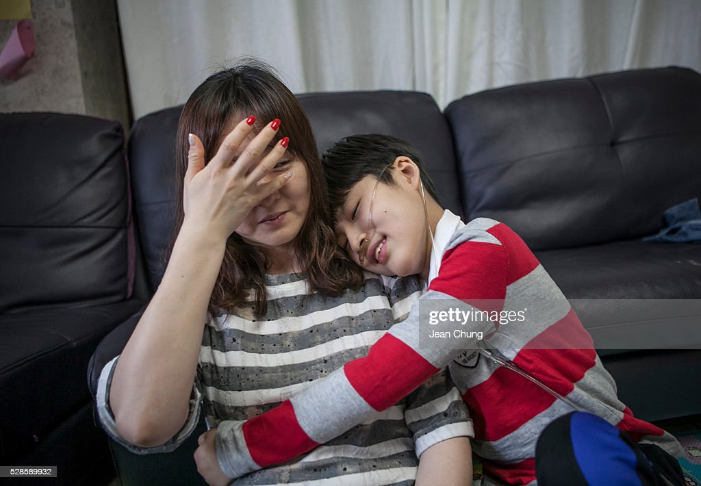 Lim Seong-joon, 13, who is suffering from chronic lung disease, comforts his tearful mother, Kwon Mi-ae on May 6, 2016 in Yongin, South Korea. His mother bought a humidifier sterilizer called 'Oxy Humidifier on Duty' back in 2003, and used the product with a humidifier for more than a year, subsequently damaging the lungs of Seong-joon. Seong-joon has gone through operations and now is living off of an oxygen tank 24 hours a day. His mother, Kwon Mi-ae, said that she thought of killing herself many times, but decided to live for him. Beginning in 2001, Reckitt Benckiser Korea (known as Oxy prior to 2014) used Polyhexamethylene guanidine (PHMG) in a humidifier sterilizer product called Oxy Ssak Ssak; the ingredient was dropped in 2011 when the Korea Centers for Disease Control and Prevention (KCDC) published a report showing a link between the compound and lung damage and deaths. Several companies in South Korea made humidifier sterliizers with poisonous ingredients between 2001 and 2011. According to a BBC report in May 2016, about 500 people, many of them women and children, are reported to have died or been injured after inhaling these ingredients. One of the victims's fathers is visiting U.K. right now, and a few other victims's families are planning to visit the U.K. at the end of May. The U.K.-based firm Reckitt Benckiser has admitted and apologized for selling a humidifier disinfectant that killed more than 100 people in South Korea on May 2, 2016.