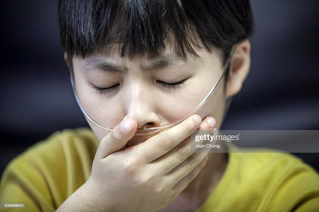 Lim Seong-joon, 13, who is suffering from chronic lung disease, covers his mouth as he coughs at home on May 6, 2016 in Yongin, South Korea. His mother bought a humidifier sterilizer called 'Oxy Humidifier on Duty' back in 2003, and used the product with a humidifier for more than a year, subsequently damaging the lungs of Seong-joon. Seong-joon has gone through operations and now is living off of an oxygen tank 24 hours a day. His mother, Kwon Mi-ae, said that she thought of killing herself many times, but decided to live for him. Beginning in 2001, Reckitt Benckiser Korea (known as Oxy prior to 2014) used Polyhexamethylene guanidine (PHMG) in a humidifier sterilizer product called Oxy Ssak Ssak; the ingredient was dropped in 2011 when the Korea Centers for Disease Control and Prevention (KCDC) published a report showing a link between the compound and lung damage and deaths. Several companies in South Korea made humidifier sterliizers with poisonous ingredients between 2001 and 2011. According to a BBC report in May 2016, about 500 people, many of them women and children, are reported to have died or been injured after inhaling these ingredients. One of the victims's fathers is visiting U.K. right now, and a few other victims's families are planning to visit the U.K. at the end of May. The U.K.-based firm Reckitt Benckiser has admitted and apologized for selling a humidifier disinfectant that killed more than 100 people in South Korea on May 2, 2016.