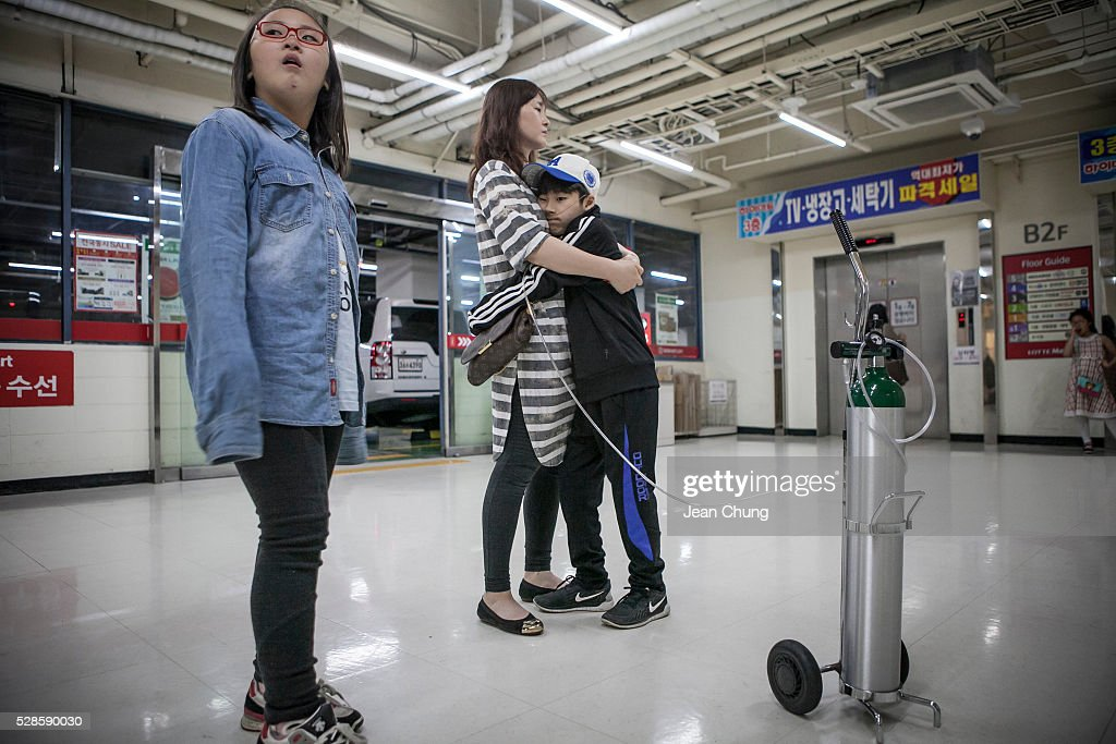 Lim Seong-joon, 13, (R) who is suffering from chronic lung disease, hugs his mother outside the elevators of a market on May 6, 2016 in Yongin, South Korea. His mother bought a humidifier sterilizer called 'Oxy Humidifier on Duty' back in 2003, and used the product with a humidifier for more than a year, subsequently damaging the lungs of Seong-joon. Seong-joon has gone through operations and now is living off of an oxygen tank 24 hours a day. His mother, Kwon Mi-ae, said that she thought of killing herself many times, but decided to live for him. Beginning in 2001, Reckitt Benckiser Korea (known as Oxy prior to 2014) used Polyhexamethylene guanidine (PHMG) in a humidifier sterilizer product called Oxy Ssak Ssak; the ingredient was dropped in 2011 when the Korea Centers for Disease Control and Prevention (KCDC) published a report showing a link between the compound and lung damage and deaths. Several companies in South Korea made humidifier sterliizers with poisonous ingredients between 2001 and 2011. According to a BBC report in May 2016, about 500 people, many of them women and children, are reported to have died or been injured after inhaling these ingredients. One of the victims's fathers is visiting U.K. right now, and a few other victims's families are planning to visit the U.K. at the end of May. The U.K.-based firm Reckitt Benckiser has admitted and apologized for selling a humidifier disinfectant that killed more than 100 people in South Korea on May 2, 2016.