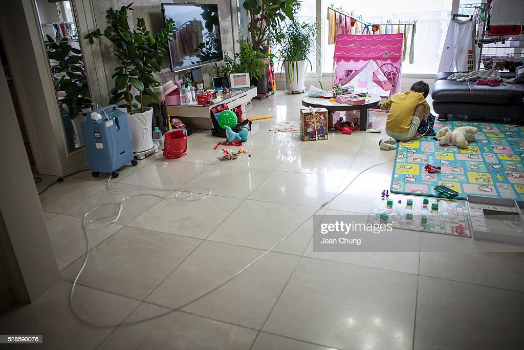Lim Seong-joon, 13, who is suffering from chronic lung disease, looks through a bag of toys while connected to an oxygen tank, (L) at home on May 6, 2016 in Yongin, South Korea. His mother bought a humidifier sterilizer called 'Oxy Humidifier on Duty' back in 2003, and used the product with a humidifier for more than a year, subsequently damaging the lungs of Seong-joon. Seong-joon has gone through operations and now is living off of an oxygen tank 24 hours a day. His mother, Kwon Mi-ae, said that she thought of killing herself many times, but decided to live for him. Beginning in 2001, Reckitt Benckiser Korea (known as Oxy prior to 2014) used Polyhexamethylene guanidine (PHMG) in a humidifier sterilizer product called Oxy Ssak Ssak; the ingredient was dropped in 2011 when the Korea Centers for Disease Control and Prevention (KCDC) published a report showing a link between the compound and lung damage and deaths. Several companies in South Korea made humidifier sterliizers with poisonous ingredients between 2001 and 2011. According to a BBC report in May 2016, about 500 people, many of them women and children, are reported to have died or been injured after inhaling these ingredients. One of the victims's fathers is visiting U.K. right now, and a few other victims's families are planning to visit the U.K. at the end of May. The U.K.-based firm Reckitt Benckiser has admitted and apologized for selling a humidifier disinfectant that killed more than 100 people in South Korea on May 2, 2016.
