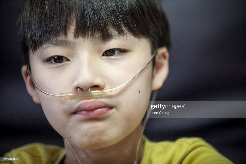 Lim Seong-joon, 13, who is suffering from chronic lung disease, rests at home on May 6, 2016 in Yongin, South Korea. His mother bought a humidifier sterilizer called 'Oxy Humidifier on Duty' back in 2003, and used the product with a humidifier for more than a year, subsequently damaging the lungs of Seong-joon. Seong-joon has gone through operations and now is living off of an oxygen tank 24 hours a day. His mother, Kwon Mi-ae, said that she thought of killing herself many times, but decided to live for him. Beginning in 2001, Reckitt Benckiser Korea (known as Oxy prior to 2014) used Polyhexamethylene guanidine (PHMG) in a humidifier sterilizer product called Oxy Ssak Ssak; the ingredient was dropped in 2011 when the Korea Centers for Disease Control and Prevention (KCDC) published a report showing a link between the compound and lung damage and deaths. Several companies in South Korea made humidifier sterliizers with poisonous ingredients between 2001 and 2011. According to a BBC report in May 2016, about 500 people, many of them women and children, are reported to have died or been injured after inhaling these ingredients. One of the victims's fathers is visiting U.K. right now, and a few other victims's families are planning to visit the U.K. at the end of May. The U.K.-based firm Reckitt Benckiser has admitted and apologized for selling a humidifier disinfectant that killed more than 100 people in South Korea on May 2, 2016.