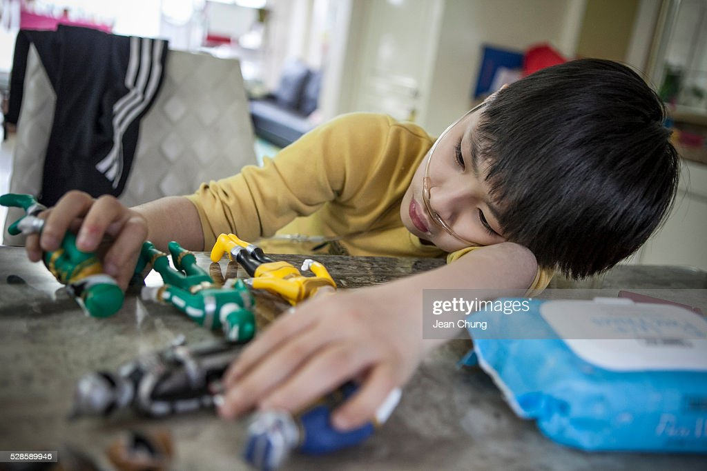 Lim Seong-joon,13, who is suffering from chronic lung disease, starts to get tired while playing with his toys as he is connected to an oxygen tank (not shown) to help him breathe on May 6, 2016 in Yongin, South Korea. His mother bought a humidifier sterilizer called 'Oxy Humidifier on Duty' back in 2003, and used the product with a humidifier for more than a year, subsequently damaging the lungs of Seong-joon. Seong-joon has gone through operations and now is living off of an oxygen tank 24 hours a day. His mother, Kwon Mi-ae, said that she thought of killing herself many times, but decided to live for him. Beginning in 2001, Reckitt Benckiser Korea (known as Oxy prior to 2014) used Polyhexamethylene guanidine (PHMG) in a humidifier sterilizer product called Oxy Ssak Ssak; the ingredient was dropped in 2011 when the Korea Centers for Disease Control and Prevention (KCDC) published a report showing a link between the compound and lung damage and deaths. Several companies in South Korea made humidifier sterliizers with poisonous ingredients between 2001 and 2011. According to a BBC report in May 2016, about 500 people, many of them women and children, are reported to have died or been injured after inhaling these ingredients. One of the victims's fathers is visiting U.K. right now, and a few other victims's families are planning to visit the U.K. at the end of May. The U.K.-based firm Reckitt Benckiser has admitted and apologized for selling a humidifier disinfectant that killed more than 100 people in South Korea on May 2, 2016.