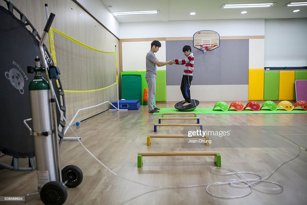 Lim Seong-joon, 13, who is suffering from chronic lung disease, takes a special gym lesson with an instructor while connected to an oxygen tank (L) on May 6, 2016 in Yongin, South Korea. His mother bought a humidifier sterilizer called 'Oxy Humidifier on Duty' back in 2003, and used the product with a humidifier for more than a year, subsequently damaging the lungs of Seong-joon. Seong-joon has gone through operations and now is living off of an oxygen tank 24 hours a day. His mother, Kwon Mi-ae, said that she thought of killing herself many times, but decided to live for him. Beginning in 2001, Reckitt Benckiser Korea (known as Oxy prior to 2014) used Polyhexamethylene guanidine (PHMG) in a humidifier sterilizer product called Oxy Ssak Ssak; the ingredient was dropped in 2011 when the Korea Centers for Disease Control and Prevention (KCDC) published a report showing a link between the compound and lung damage and deaths. Several companies in South Korea made humidifier sterliizers with poisonous ingredients between 2001 and 2011. According to a BBC report in May 2016, about 500 people, many of them women and children, are reported to have died or been injured after inhaling these ingredients. One of the victims's fathers is visiting U.K. right now, and a few other victims's families are planning to visit the U.K. at the end of May. The U.K.-based firm Reckitt Benckiser has admitted and apologized for selling a humidifier disinfectant that killed more than 100 people in South Korea on May 2, 2016.