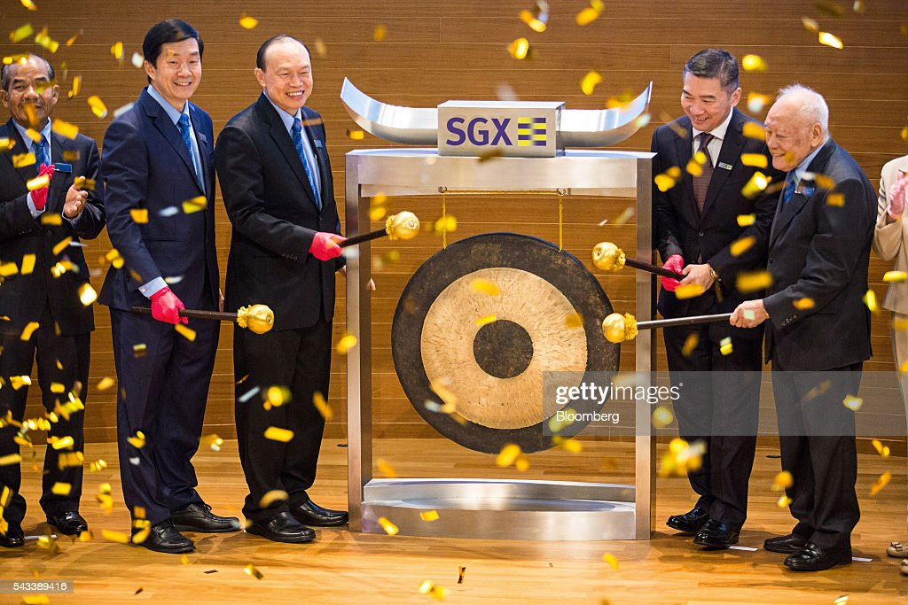Lim Wee Chai, co-founder and chairman of Top Glove Corp., third left, strikes a gong during the listing of the company at the Singapore Stock Exchange in Singapore, on Tuesday, June 28, 2016. Top Glove made its trading debut at the Singapore Exchange Securities Trading Ltd. (SGX-ST) today. Photographer: Nicky Loh/Bloomberg via Getty Images