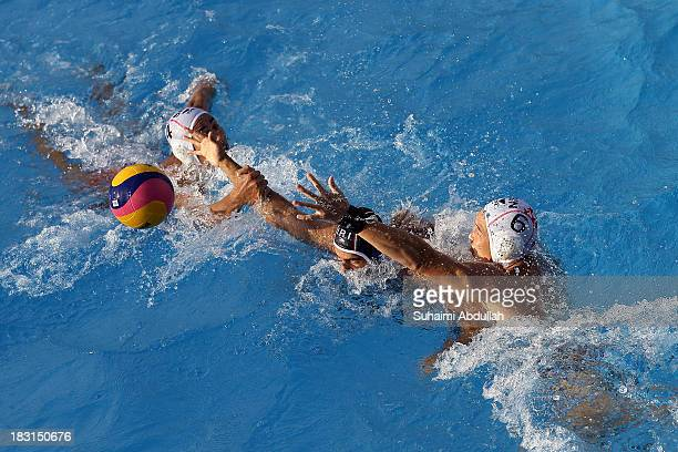 Lim Yao Xiang of Singapore Amirhossein Ghahjavarestani Khani of Iran and Paul Tan of Singapore challenge for the ball during the finals of the Asian...