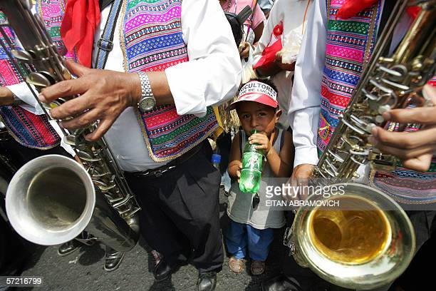A boy peers between musicians as farmers celebrate in Lima 30 March 2006 the land grants given by the Peruvian congress the same day a national...