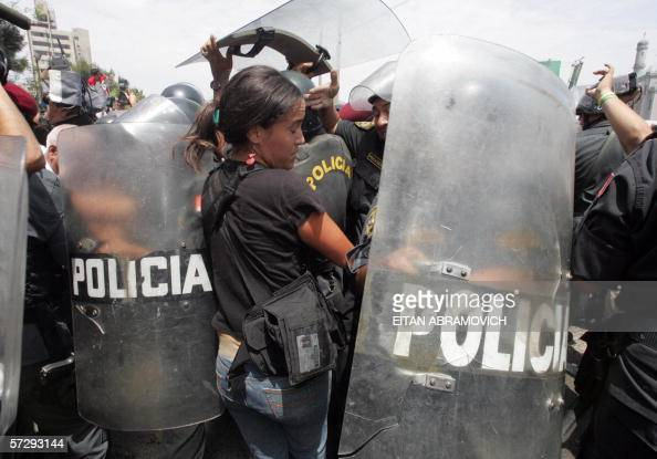 A photojournalist is pushed away with their shields by riot police clearing an exit path for presidential candidate former army lieutenant colonel...