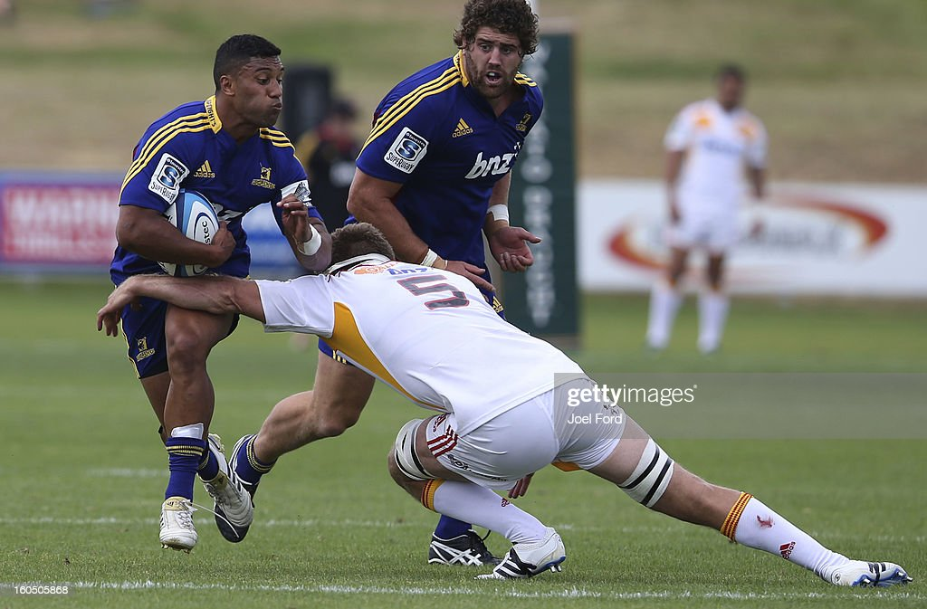Lima Sopoaga of the Highlanders tries to break the tackle of Michael Fitzgerald of the Chiefs during the 2013 Super Rugby pre-season friendly match between the Chiefs and the Highlanders at Owen Delany Park, Taupo on February 2, 2013 in Taupo, New Zealand.