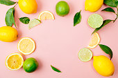 Flat lay of citrus fruits like lime and lemon with lemon tree leaves on light pink background making a frame